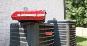 A toolbox sitting on top of an heating and cooling unit in need of repairs.